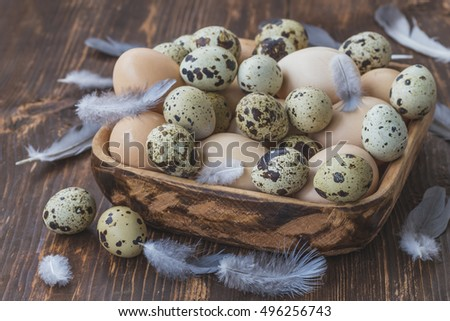 Quail and chicken eggs in a wooden bowl