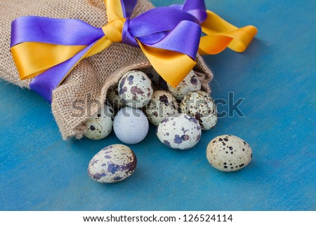 quail egg in bag with ribbon on blue table