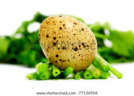 Quail egg on the salad sheet, isolated on a white background