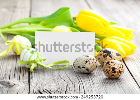 Quail eggs and Easter eggs on wooden background - stock photo