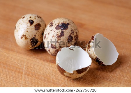 Quail eggs and eggshell on woody background, healthy food concept - stock photo