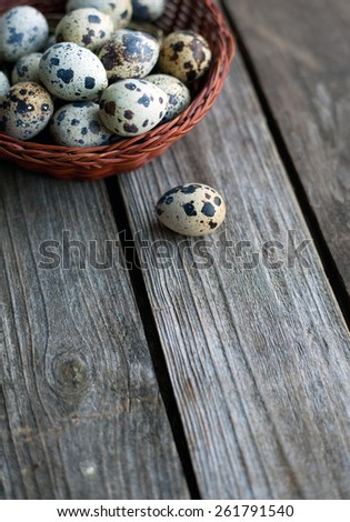 Quail eggs in a basket on a rustic wooden table - stock photo