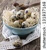 quail eggs in a blue bowl on a wooden board - stock photo