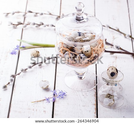 Quail eggs in a nest, in a glass vase.Easter decorations. - stock photo
