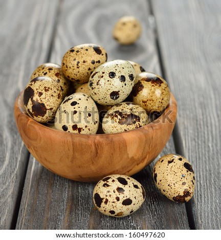 quail eggs in a wooden bowl on a gray background