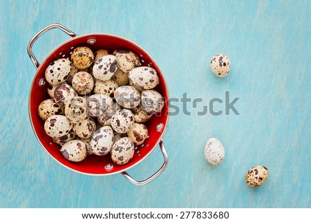 Quail eggs in red colander on a blue wooden background, top view - stock photo