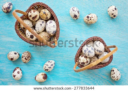 Quail eggs in two pleated wooden buckets in shape of heart on blue wooden background, top view - stock photo