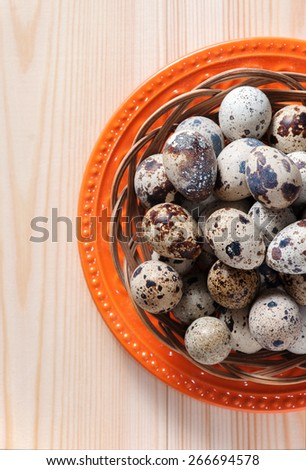 Quail eggs in wicker bowl and orange plate, standing on wooden boards, top view, crop - stock photo