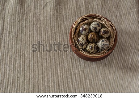 Quail eggs  on a wooden bowl and gray background