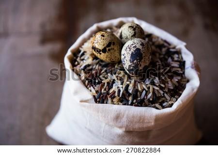 quail eggs on rice in sacks - stock photo