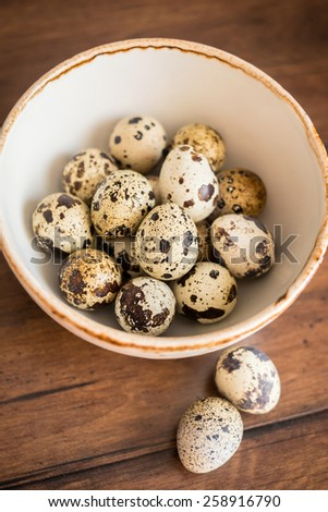 Quail eggs on the wooden vintage table, selective focus  - stock photo