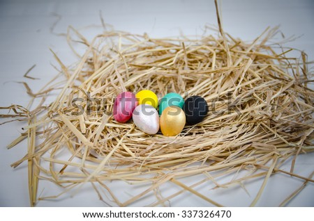 Quail eggs painted by Kids crafts for Easter Eggs, Handmade of Color poster painted on nest grass. - stock photo