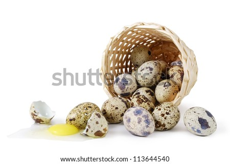 Quail eggs scattered from a basket and one broken.