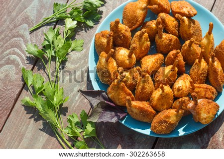 Quail legs fried in batter. At the plate, on a wooden background. - stock photo