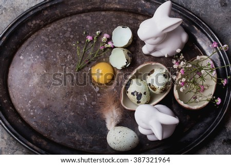 Quails Eggs  and white ceramic bunny with flowers on an old vintage metal tray against a rustic background with selective focus. A different type of concept image for Easter. - stock photo