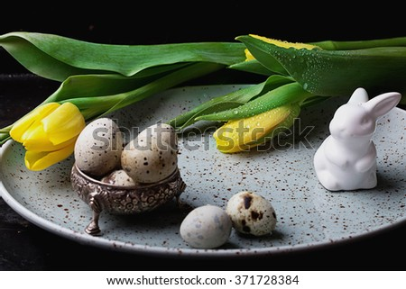 Quails Eggs  and white ceramic bunny with yellow tulip flowers on an old spotted plate against a rustic background with selective focus. A different type of concept image for Easter.
