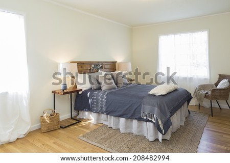 Quaint Bedroom at twilight in beige with chair, bedside lamps, natural fiber rug and vintage furniture. - stock photo