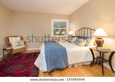 Quaint Bedroom at twilight in beige with chair, bedside lamps, red ornamented rug and vintage furniture. - stock photo