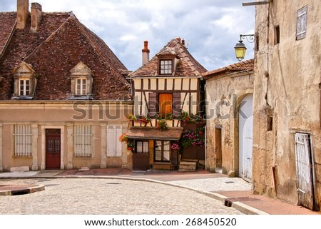 Quaint street in a town in Burgundy, France with small timbered house - stock photo