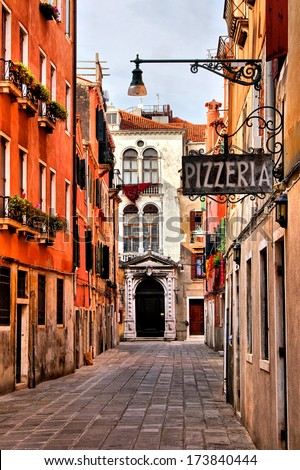Quaint street in historic Venice, Italy with Pizzeria sign - stock photo