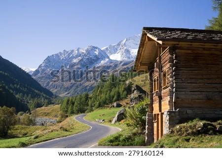 Quaint Wood Cabin Beside Paved Single Lane Mountain Road Through Snow Capped Alps, Valais, Switzerland. - stock photo