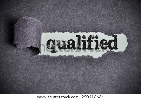qualified word under torn black sugar paper  - stock photo