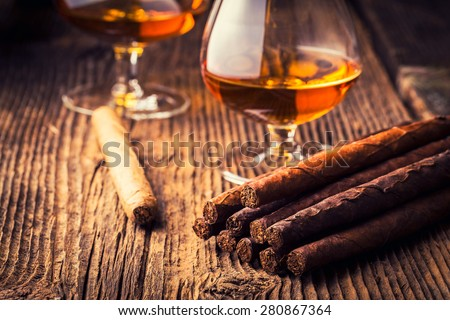 quality cigars and cognac on an old wooden table - stock photo