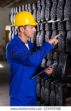quality controller checking quality of gumboots - stock photo