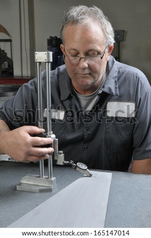 Quality Inspector using a precision measuring gauge in a production machine shop - stock photo