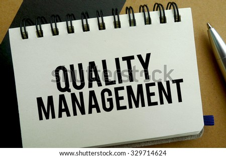 Quality management memo written on a notebook with pen