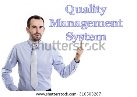 Quality Management System QMS - Young businessman with small beard pointing up in blue shirt