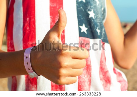 Quality sign -  thumb up. It's ok! I am satisfied! Summertime outdoors. - stock photo