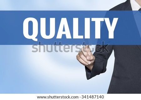 Quality word on virtual screen touch by business woman blue background - stock photo