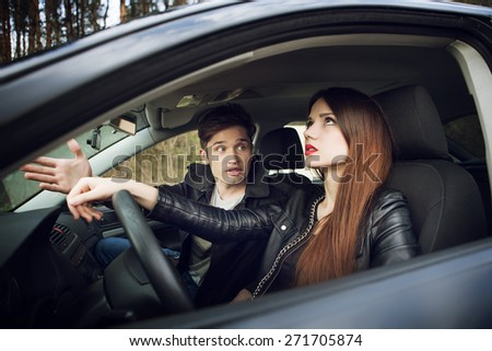 quarrel in the car, the couple quarrel in the car, the woman behind the wheel of a car - stock photo