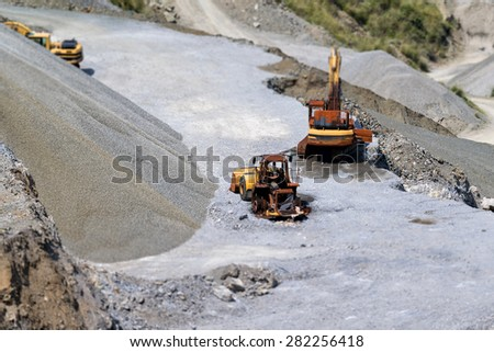 quarry and bulldozers with tilt shift effect - stock photo