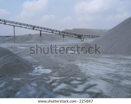 quarry conveyor belt with mounds of stones - stock photo