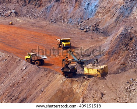 Quarry excavator load the iron ore to big dump truck in openpit mine with another two trucks waiting in queue