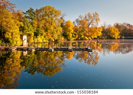 Quarry Lake Autumn Golden fall color is reflected in the calm surface of Quarry Lake in downtown Naperville, Illinois. - stock photo