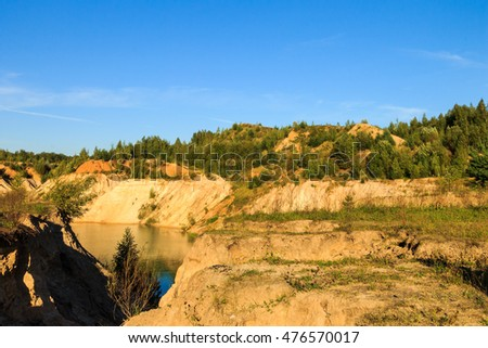 quarry or lake or pond with sandy beach, green water, trees and hills with blue sky at summer season