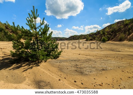 quarry with sandy beach,trees and hills with cloudly sky at summer season