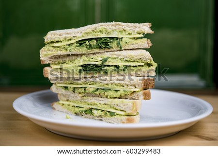 Quartered and stacked avocado and fresh lettuce sandwich on a white plate viewed from the side