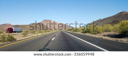 QUARTZSITE, US - APRIL 17, 2015: Buttes and low rise mountains along Interstate-10 east of city of Quartzsite.in Arizona desert covered with drought and extreme heat resistant vegetation. - stock photo