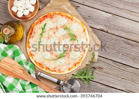 Quattro fromaggi pizza with lettuce on wooden table. Top view with copy space - stock photo