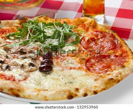 Quattro Stagioni (four seasons) pizza on a restaurant table. Studio shot - stock photo