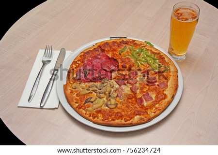 Quattro stagioni (four seasons) type of pizza with mushrooms, sausage, green pepper and ham, place setting for one and a cold beer