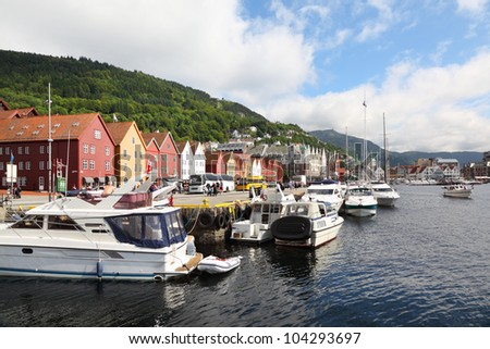 Quay in dock with boats at coastal Bergen town, citizens walk down street