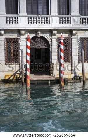 quay on the Grand Canal with typical red and white mooring poles, venice italy - stock photo