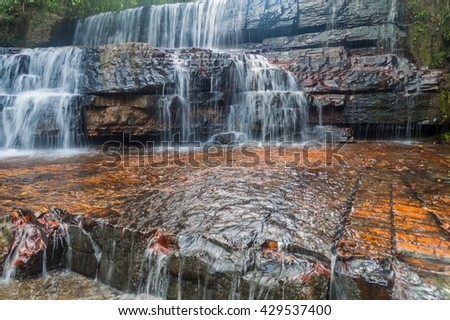 Qubrada de Jaspe (Jasper Creek) is the river and a series of cascades in National Park Canaima, Venezuela. The water flows over a bedrock of jasper. - stock photo