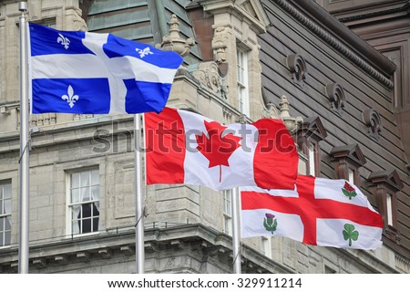 Quebec, Canadian and Montreal flags waving with the foreground of City Hall of Montreal, Quebec, Canada - stock photo