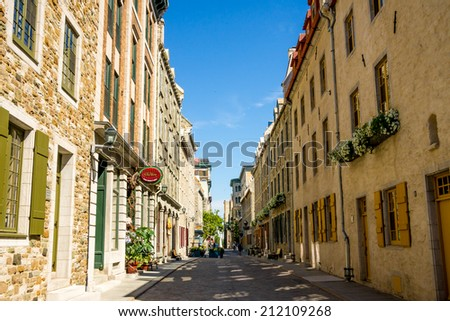 QUEBEC CITY, CANADA- JULY 10 2011: Street of old Quebec with boutique, restaurant, and residence, typically of Quebec City.  - stock photo